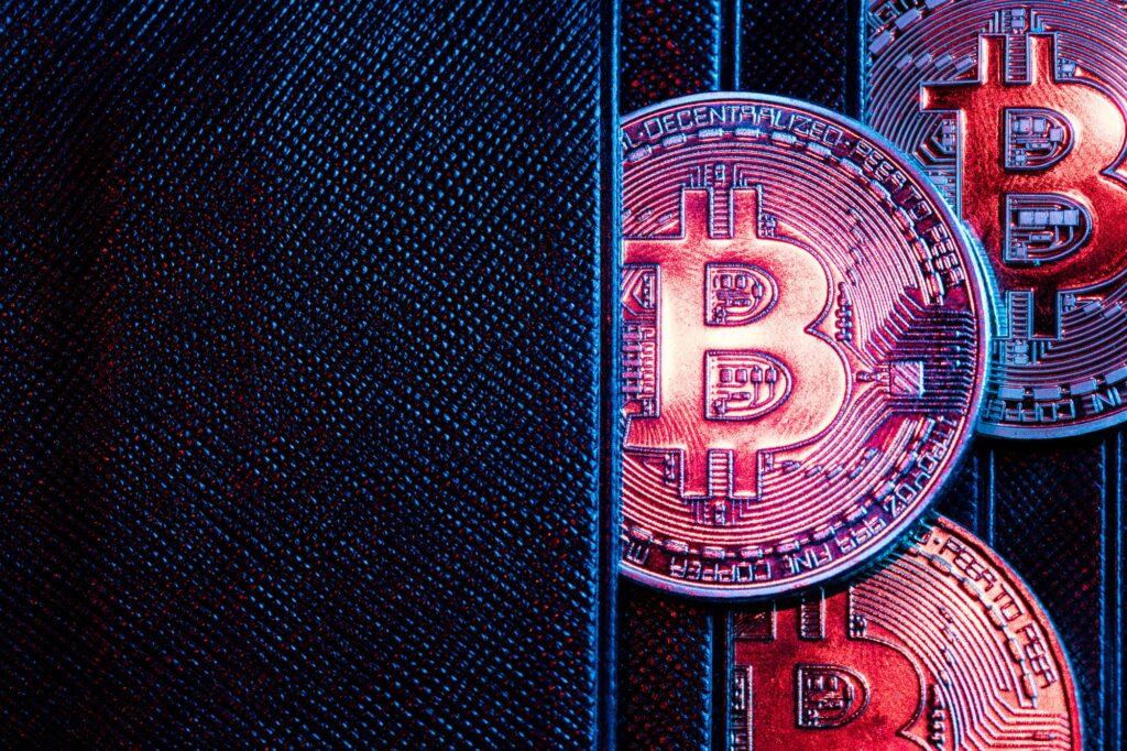 Bitcoin coins sticking out of a wallet.